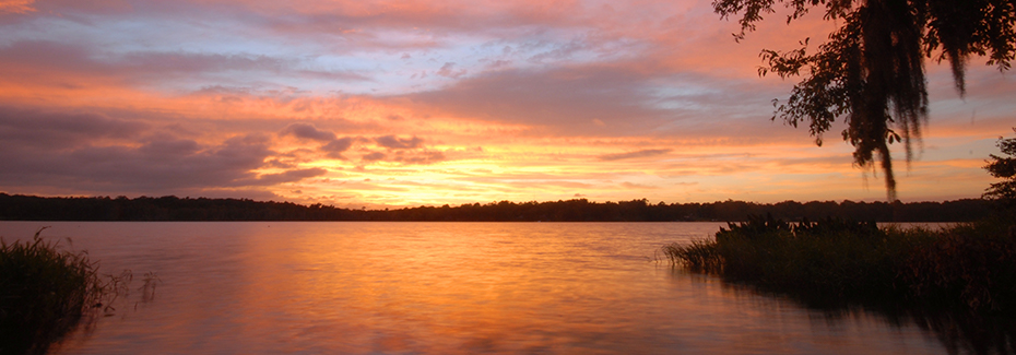 Sun rising over a lake which reflects the oranges and pinks of the sunrise